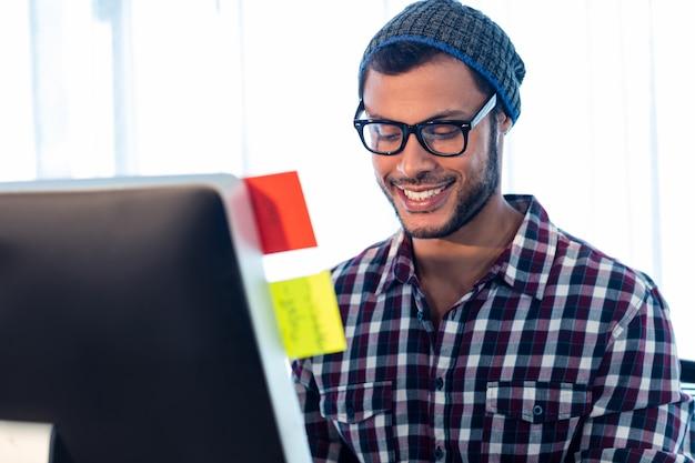 Ritratto dell'uomo sorridente dei pantaloni a vita bassa che lavora allo scrittorio Foto Premium