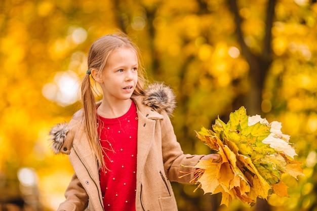 Ritratto della bambina adorabile con il mazzo delle foglie di giallo nella caduta Foto Premium