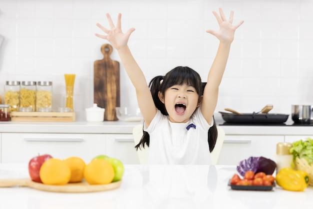 Ritratto della bambina asiatica che sorride nella cucina Foto Premium