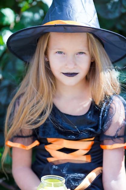 Ritratto della bambina sveglia che porta il costume della strega con la scopa su halloween Foto Premium