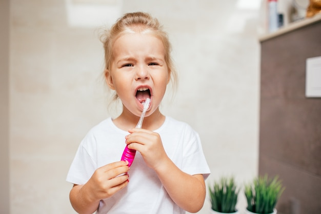 Ritratto della bambina sveglia con capelli biondi quale dente di pulizia con la spazzola e dentifricio in bagno. copyspace Foto Premium