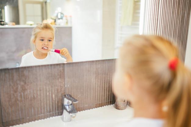 Ritratto della bambina sveglia con capelli biondi quale dente di pulizia con la spazzola e dentifricio in bagno vicino allo specchio. Foto Premium