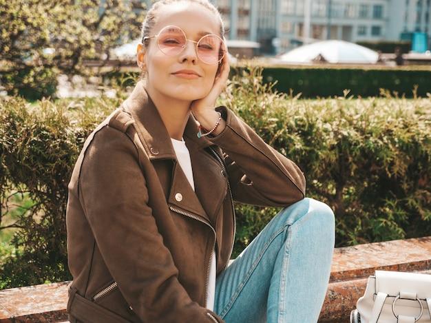 Ritratto della bellissima modella bruna sorridente vestita in abiti hipster estate giacca e jeans ragazza alla moda, seduto sulla panchina in strada Foto Gratuite