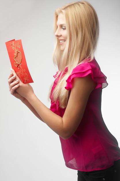 Ritratto della carta felice del biglietto di s. valentino della tenuta della giovane donna Foto Premium