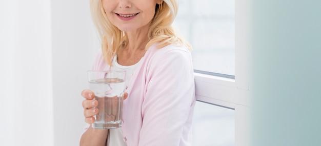 Ritratto della donna abbastanza matura che tiene un bicchiere d'acqua Foto Gratuite