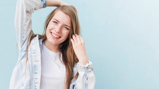Ritratto della donna attraente sorridente sulla parete blu Foto Gratuite