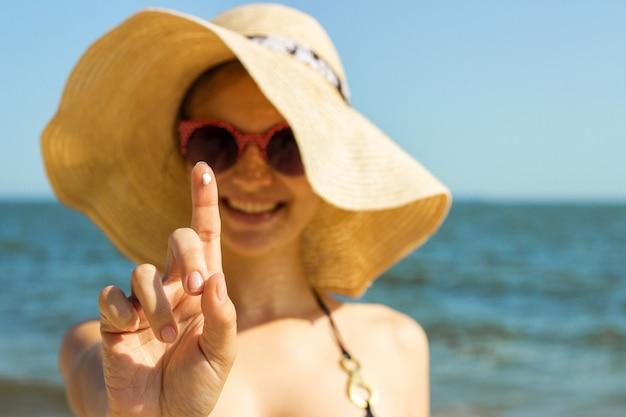 Ritratto della donna che cattura skincare con crema solare in spiaggia Foto Premium