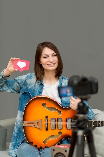 Ritratto della donna che registra video musicale a casa Foto Gratuite