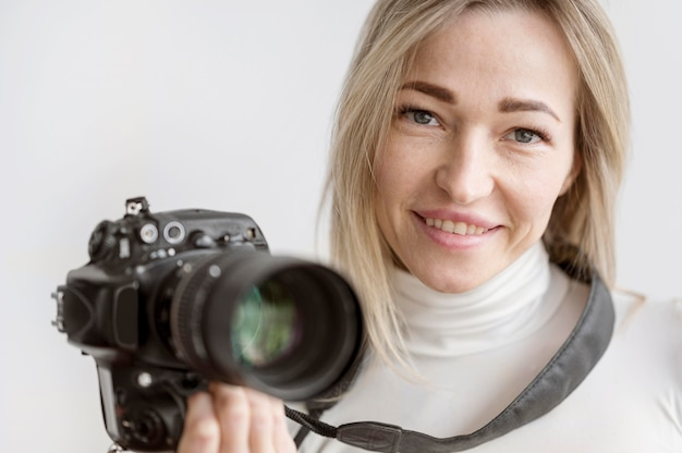 Ritratto della donna che tiene una foto della macchina fotografica Foto Gratuite