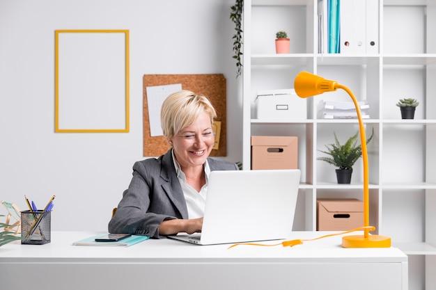 Ritratto della donna di affari invecchiata centrale in ufficio Foto Gratuite