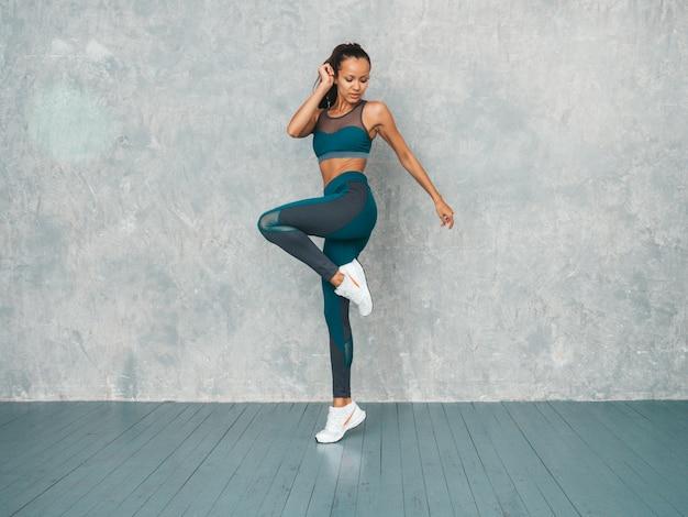 Ritratto della donna di forma fisica in abbigliamento sportivo che sembra sicuro. giovane femmina che indossa abiti sportivi bello modello con il corpo abbronzato perfetto salto femminile nello studio vicino alla parete grigia Foto Gratuite