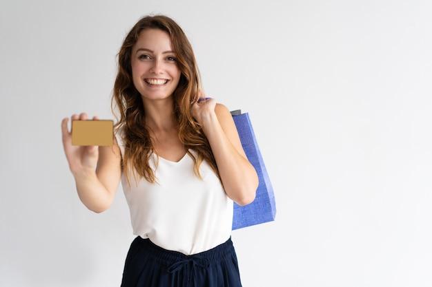 Ritratto della donna felice con i sacchetti della spesa che mostrano la carta di credito Foto Gratuite