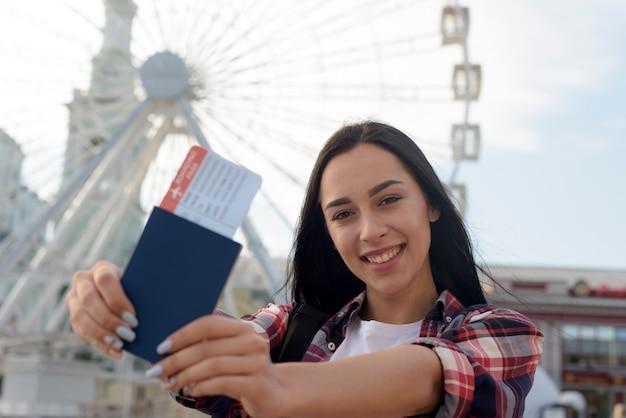 Ritratto della donna sorridente che mostra biglietto aereo e passaporto Foto Gratuite