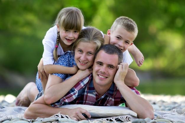 Ritratto della famiglia di giovane madre felice, padre e due bambini biondi svegli, ragazzo e ragazza il giorno di estate luminoso Foto Premium