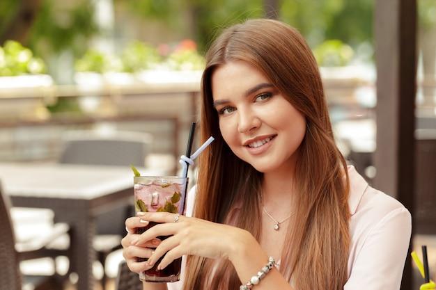 Ritratto della giovane donna deliziosa che tiene vetro di cocktail rinfrescante freddo Foto Premium