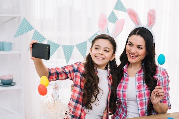 Ritratto della madre e della figlia sorridenti con le orecchie del coniglietto sulla testa che prende selfie sul telefono cellulare Foto Gratuite