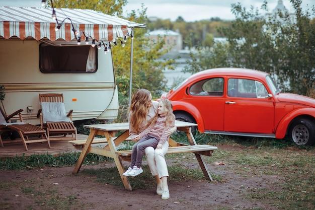 Ritratto della madre e della piccola figlia che abbracciano e che si rilassano nella campagna sulla vacanza del camper con la retro automobile rossa Foto Premium