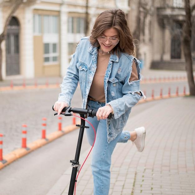 Ritratto della ragazza alla moda che guida motorino elettrico Foto Gratuite