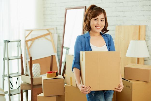 Ritratto della ragazza asiatica che tiene una scatola di cartone e che esamina macchina fotografica Foto Gratuite