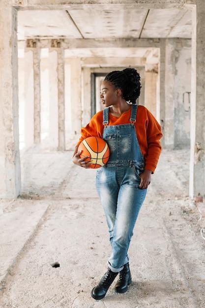 Ritratto della ragazza che propone con la sfera di pallacanestro Foto Gratuite