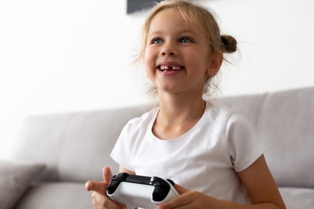 Ritratto della ragazza del bambino in età prescolare con la bocca aperta senza dente di latte Foto Premium