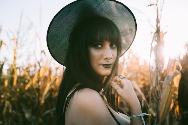 Ritratto della ragazza della strega del costume di halloween in un campo di mais al tramonto. bella giovane donna seria in cappello delle streghe con lunghi capelli neri e labbra scure Foto Premium