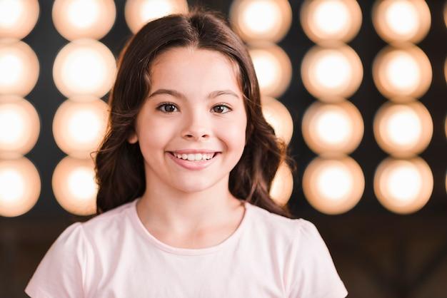 Ritratto della ragazza sorridente contro luce incandescente della fase Foto Gratuite
