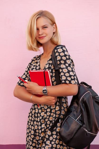 Ritratto della ragazza sorridente dello studente di modo con lo zaino nero e la tenuta della latteria rossa Foto Premium