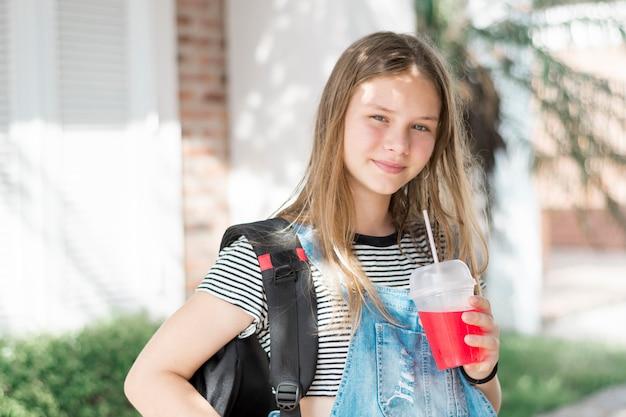 Ritratto della ragazza splendida sorridente che esamina macchina fotografica con la bevanda e la borsa fredde della tenuta Foto Gratuite