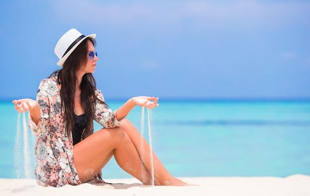 Ritratto della sabbia di lancio della giovane donna sulla spiaggia durante le vacanze estive Foto Premium