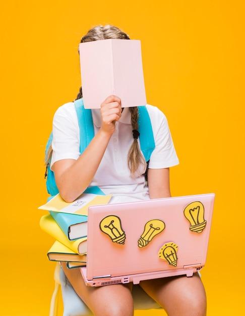 Ritratto della scolara che studia con il computer portatile Foto Gratuite