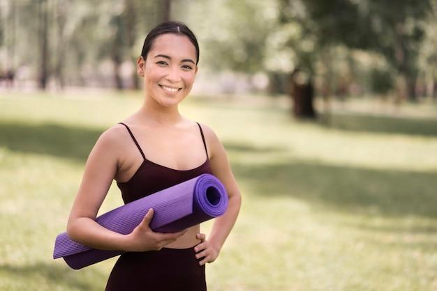 Ritratto della stuoia attiva di yoga della tenuta della donna Foto Gratuite