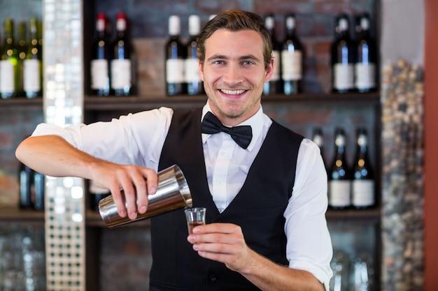 Ritratto della tequila di versamento del barista nel bicchierino Foto Premium