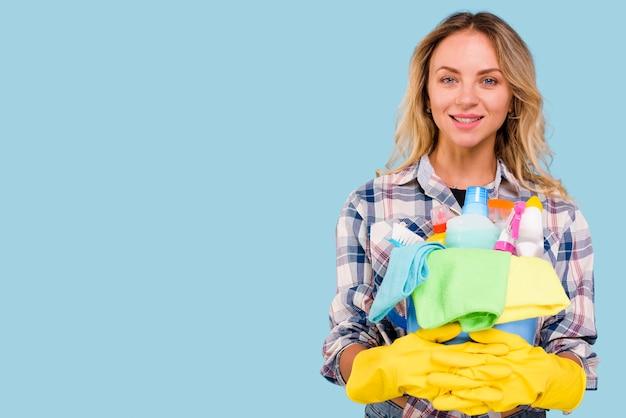 Ritratto delle attrezzature per la pulizia diritte dalla donna felice della governante nella superficie del blu Foto Gratuite