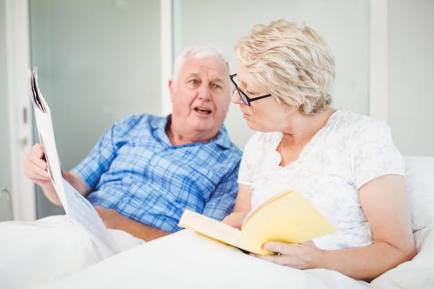 Ritratto delle coppie senior che leggono sul letto Foto Premium