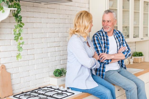 Ritratto delle coppie senior che si siedono sul contatore di cucina che se lo esamina Foto Gratuite
