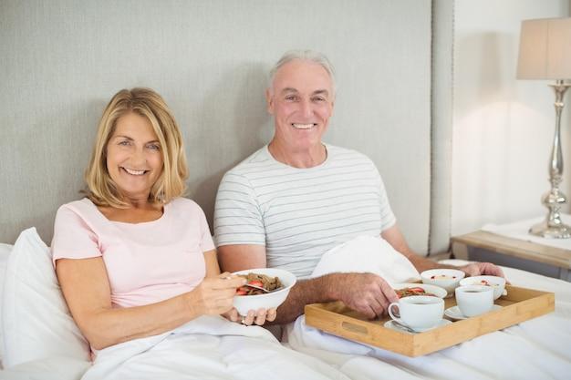 Ritratto delle coppie sorridenti che mangiano prima colazione sul letto Foto Premium