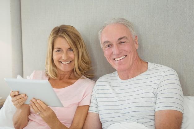 Ritratto delle coppie sorridenti facendo uso della compressa digitale sul letto Foto Premium