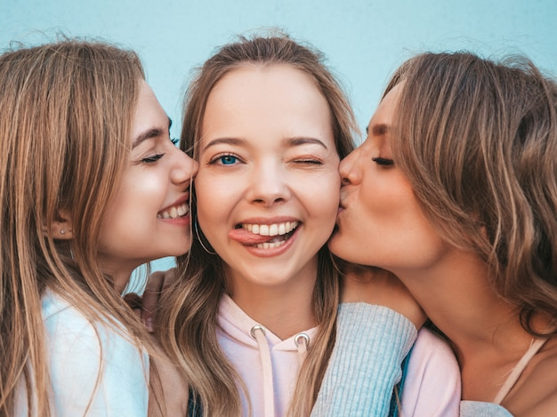 Ritratto delle donne spensierate sexy che posano nella via. modelli positivi che baciano il loro amico in guancia Foto Gratuite