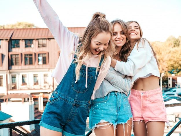 Ritratto delle donne spensierate sexy che posano sui precedenti della via divertiresi dei modelli positivi abbracciare Foto Gratuite