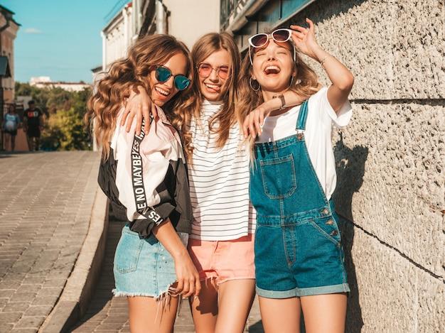 Ritratto delle donne spensierate sexy che posano sui precedenti della via modelli positivi divertendosi in occhiali da sole abbracciare Foto Gratuite