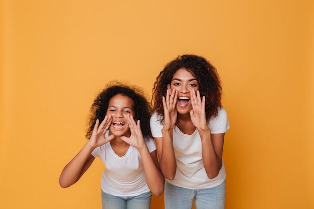 Ritratto delle due sorelle afroamericane allegre che gridano Foto Gratuite
