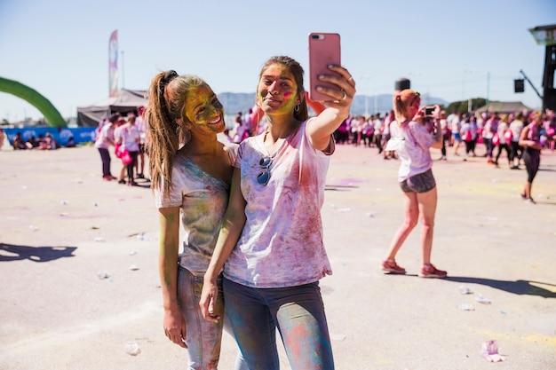 Ritratto delle giovani donne sorridenti che prendono selfie sul telefono cellulare Foto Gratuite