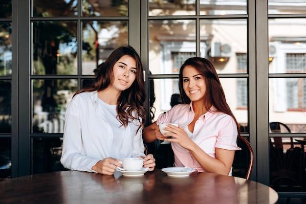 Ritratto delle ragazze che si siedono nel ristorante con la tazza a disposizione Foto Premium