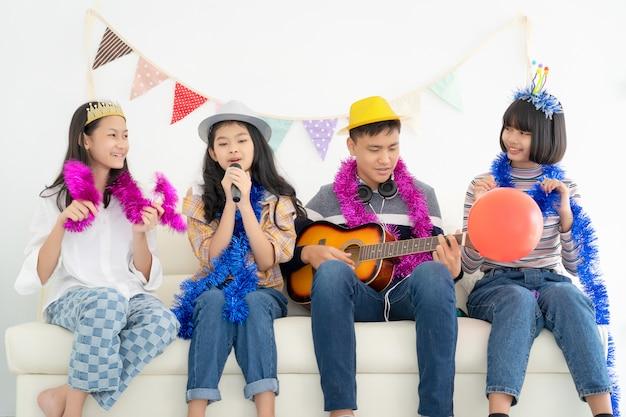 Ritratto di adolescenti felici, suonare la chitarra circondata da amici Foto Premium