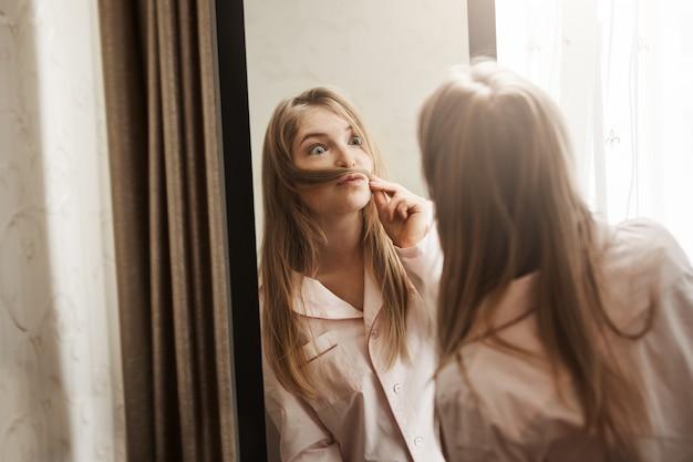 Ritratto di adorabile giocosa donna bionda che fa i baffi ...