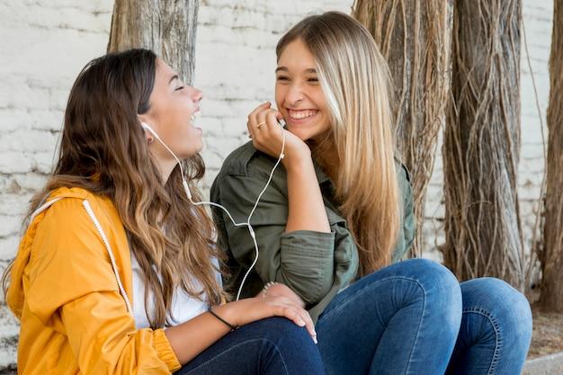 Ritratto di amici femminili sorridenti che condividono musica Foto Gratuite