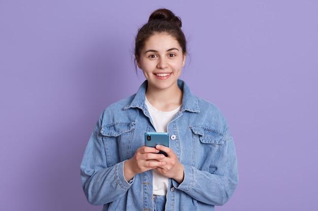 Ritratto di attraente donna caucasica indossa elegante giacca di jeans, in piedi al coperto contro il muro lilla con il moderno smartphone nelle mani, Foto Premium