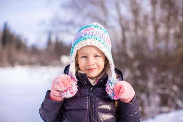 Ritratto di bambina adorabile in cappello di inverno nella foresta nevosa Foto Premium
