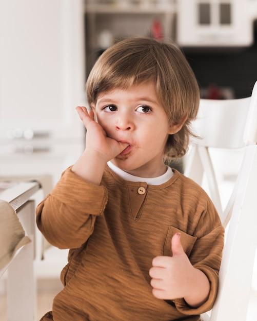 Ritratto di bambino che lecca le dita Foto Gratuite
